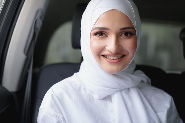 Belle Femme Musulmane En Hijab Blanc Assis Sur Le Siège Arrière D'une Voiture De Luxe Photo Premium