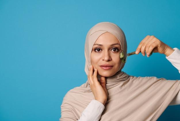 Belle femme musulmane en hijab massant son visage avec un rouleau de jade. portrait de beauté isolé