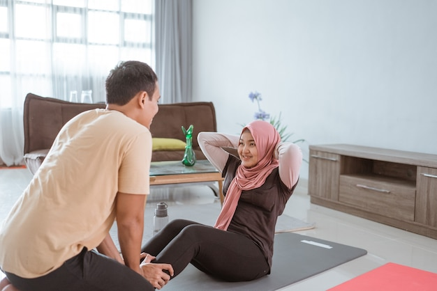 Belle femme musulmane et mari faisant s'asseoir ensemble. couple exerçant à la maison