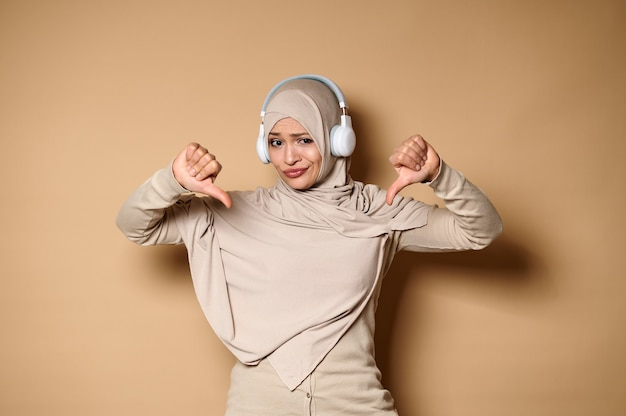 Belle femme musulmane portant le hijab et des écouteurs montrant les pouces vers le bas à la caméra, debout contre le beige.