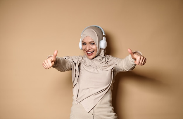 Belle femme musulmane portant le hijab et des écouteurs montrant les pouces vers la caméra, debout contre le beige.