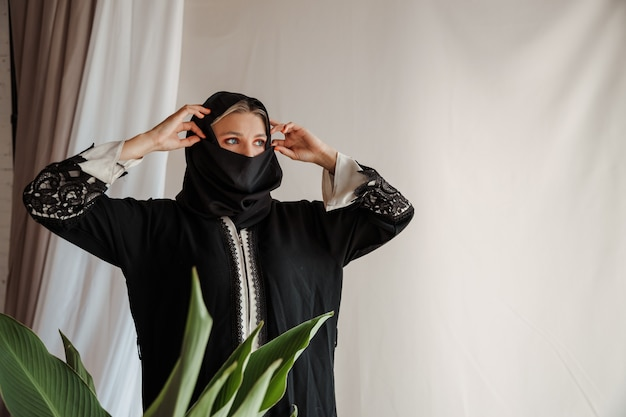 Belle femme musulmane en robe abaya arabe traditionnelle sur fond gris