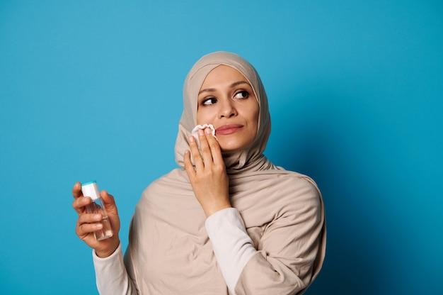 Belle femme musulmane avec tête couverte en hijab appliquant une lotion micellaire et démaquillant ses lèvres.