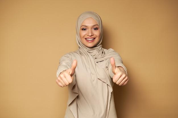 Belle femme musulmane avec tête couverte en hijab mignon souriant avec sourire à pleines dents et montrant les pouces vers le haut tout en regardant vers l'avant