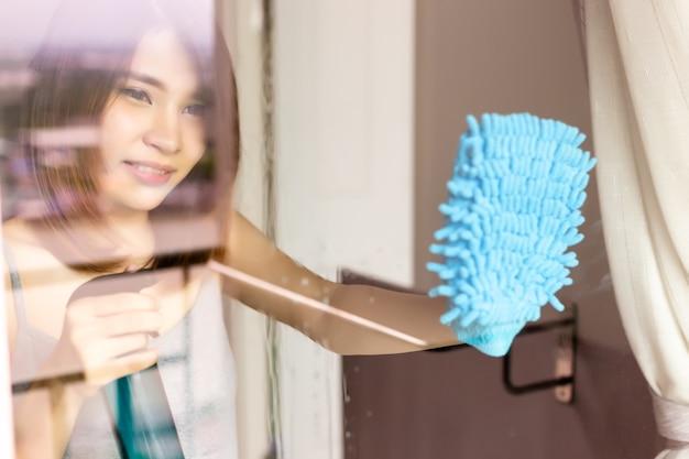 Belle femme nettoie le miroir de la porte en verre en utilisant des lingettes ou un chiffon de nettoyage