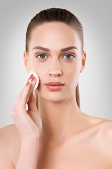 Belle femme nettoie le visage avec un coton-tige