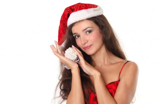 Belle femme de noël en bonnet rouge tenant la décoration de noël