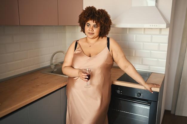 Belle femme noire africaine courbée taille plus cheveux afro buvant du vin rouge sur un scandinave moderne