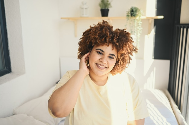 Belle femme noire africaine sinueuse heureuse taille plus cheveux afro posant en t-shirt beige et sous-vêtements