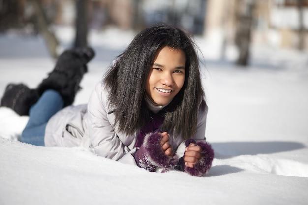 Belle femme noire américaine souriante couchée dans la neige à l'extérieur