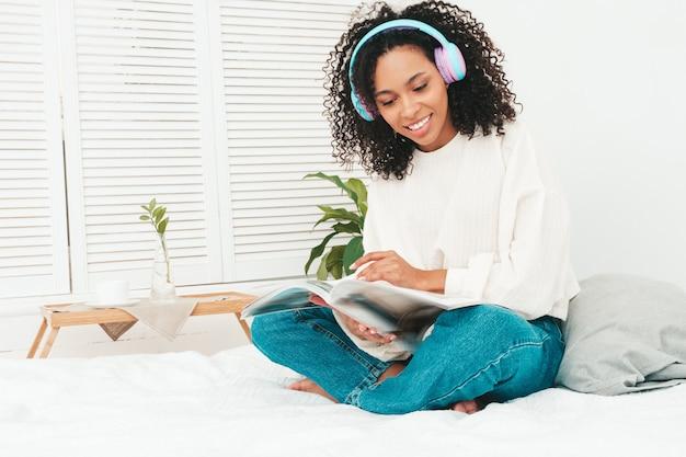 Belle femme noire avec une coiffure de boucles afro. modèle souriant en pull et jeans