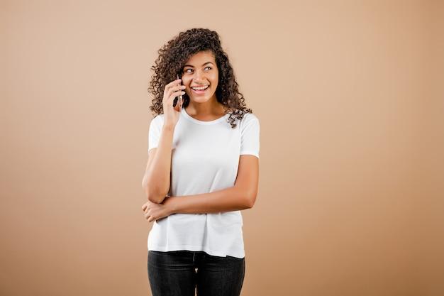 Belle femme noire parlant au téléphone isolé sur marron