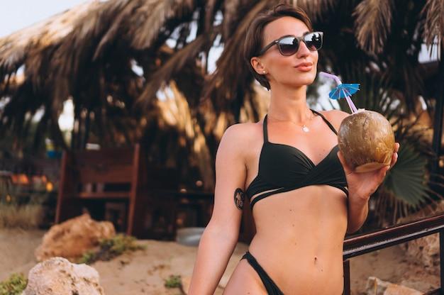 Belle femme avec de la noix de coco au bar