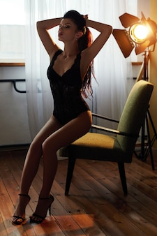 Belle femme nue aux longs cheveux noirs est assise sur une chaise. corps parfait peau propre et lisse et longues jambes. la jeune fille attend un être cher le soir sur la chaise
