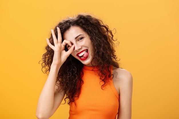 Belle femme optimiste et énergique insouciante avec une coiffure frisée inclinant la tête et tirant la langue de manière ludique montrant un signe correct ou excellent sur l'œil posant près d'un fond orange.