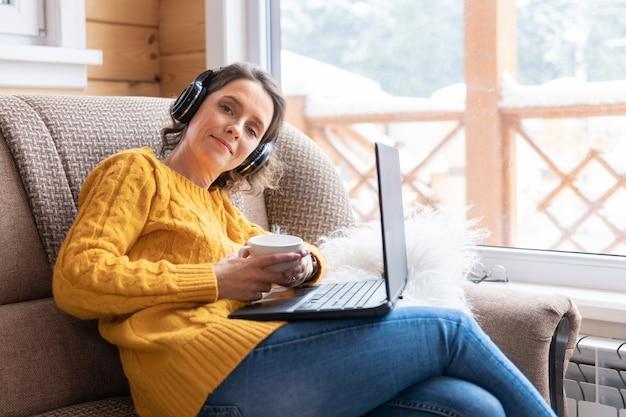 Une belle femme avec un ordinateur portable est assise sur le canapé près de la fenêtre de son appartement. elle travaille et regarde l'actualité sur les réseaux sociaux. elle avec des écouteurs écoutant de la musique