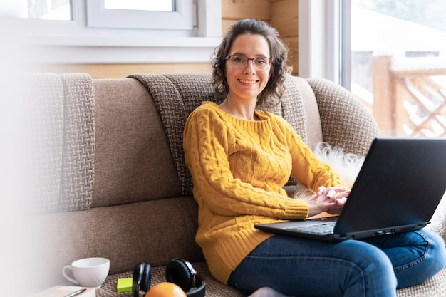 Une belle femme avec un ordinateur portable est assise sur le canapé près de la fenêtre de son appartement. elle travaille et regarde l'actualité sur les réseaux sociaux. elle avec des lunettes sourit.