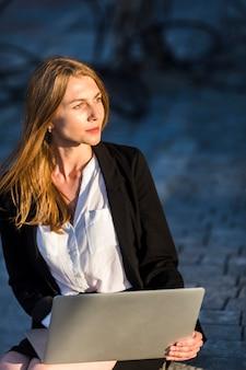Belle femme avec un ordinateur portable à l'extérieur