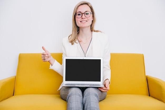 Belle femme avec ordinateur portable gesticulant thumb-up