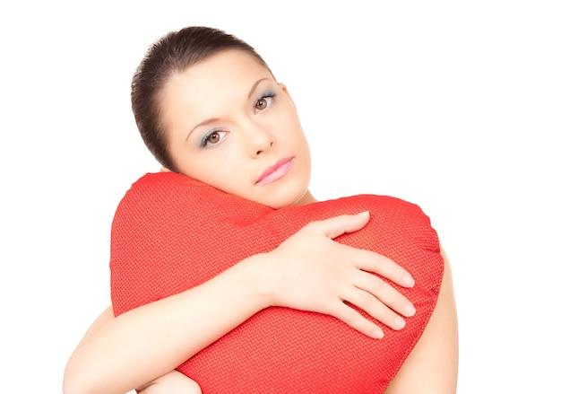 Belle femme avec un oreiller en forme de coeur rouge sur un mur blanc