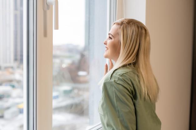 Belle femme ouvrant la fenêtre le matin
