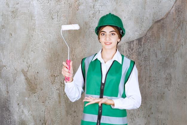 Belle femme ouvrier du bâtiment avec rouleau de peinture debout