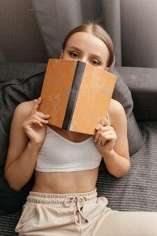 Belle femme en pantalon et un haut couvrant son visage avec un livre