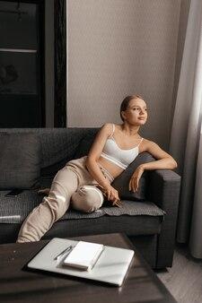Une belle femme en pantalon et un haut est allongé sur le canapé, a fini de lire un livre, regarde par la fenêtre et souriant