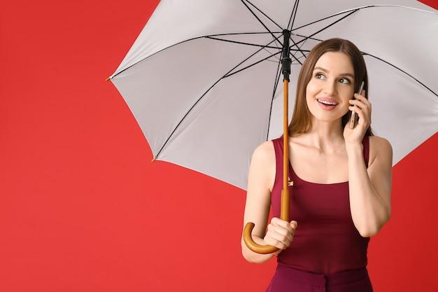 Belle femme avec parapluie parlant par téléphone mobile sur la couleur