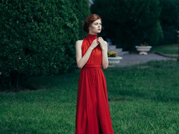 Belle femme sur le parc de robe rouge look attrayant de luxe