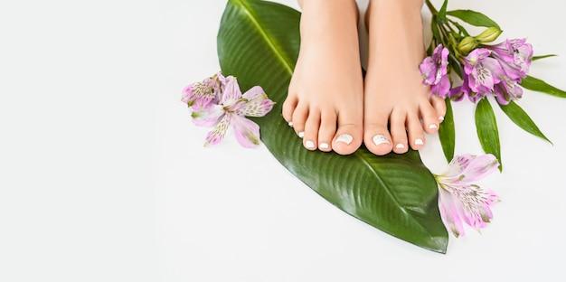 Belle femme parfaite peau jambes pieds vue de dessus avec des fleurs tropicales et feuille de palmier vert