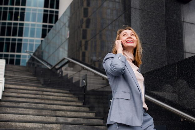 Belle femme parlant au téléphone marchant dans la rue