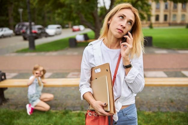 Belle femme parlant au téléphone mobile tout en pensant à quelque chose d'important du travail