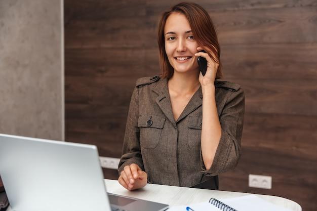 Belle femme parlant sur un téléphone portable et regardant la caméra avec un sourire. fille travaillant à la maison