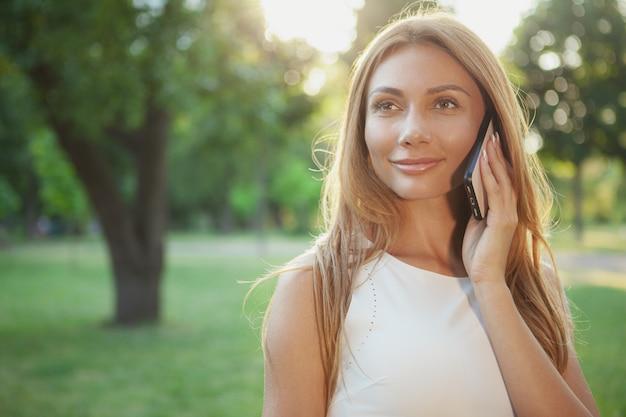 Belle femme parle au téléphone à l'extérieur