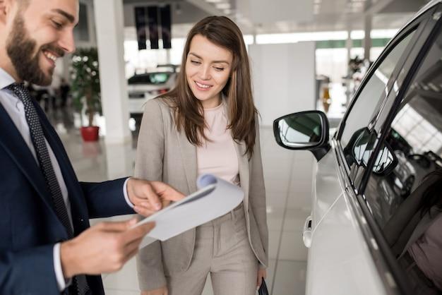 Belle femme parler au vendeur dans la salle d'exposition de voitures