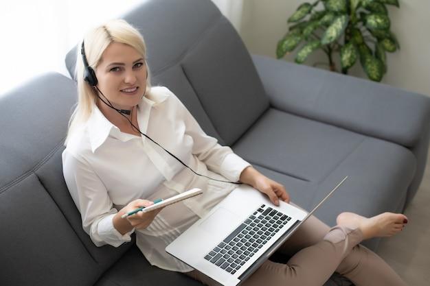 Belle femme passant en revue sa leçon avec son ordinateur portable et livre