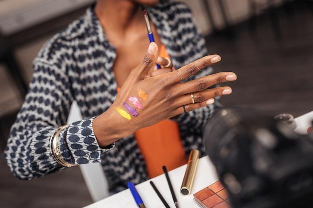Belle femme à la peau foncée avec un bracelet en or mettant de nouveaux échantillons sur sa main