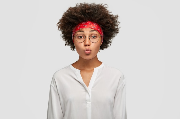 Belle femme à la peau foncée fait la moue des lèvres, a une coupe de cheveux afro, fait la grimace, porte des lunettes rondes, un bandeau rouge et une chemise blanche, se tient contre le mur. concept d'expressions faciales