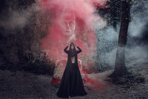 Une belle femme à la peau pâle dans une robe noire et à la couronne noire. look gothique. tenue pour halloween. une femme avec de la fumée colorée contre la sculpture d'une idole