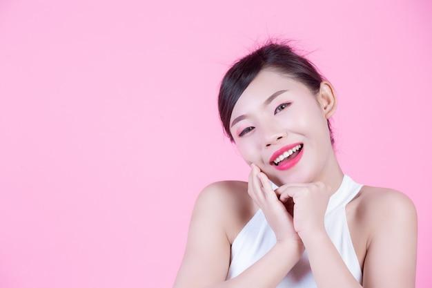 Belle femme avec une peau saine et beauté sur un fond rose.