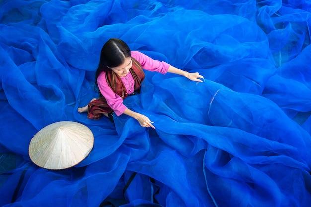 Belle femme pêcheur répare des filets de pêche, pêcheur nettoie la pêche thaïlandaise
