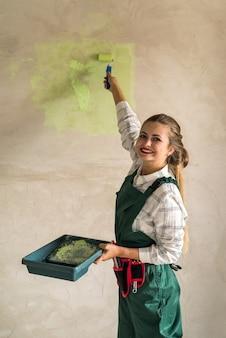 Belle femme peignant les murs avec plateau et rouleau