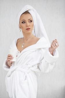 Belle femme en peignoir blanc avec une serviette sur la tête, boire du café du matin