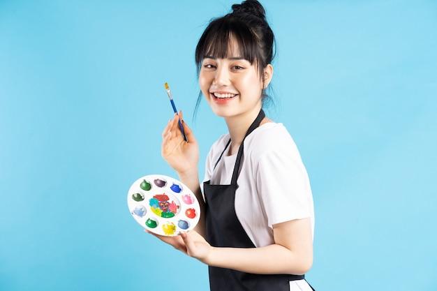 Belle femme peintre asiatique tenant plume et palette de couleurs sur bleu