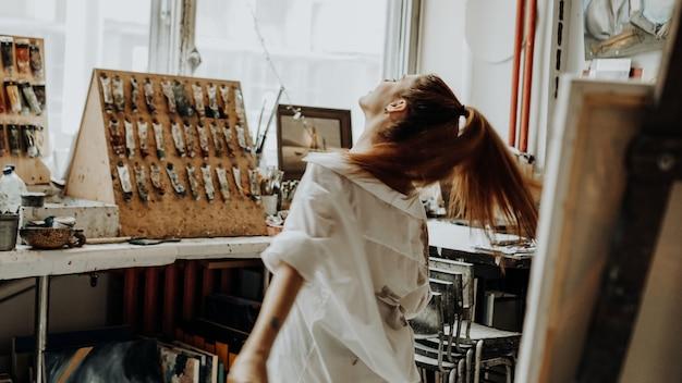Belle femme peintre vêtue d'une chemise blanche dansant tout en peignant dans un atelier d'art. mise au point sélective. photo de style vintage