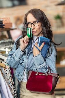 Belle femme pensant au nombre de sacs à main qu'elle peut se permettre d'acheter dans le magasin.