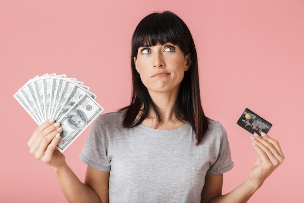Une belle femme pensante étonnante posant isolée sur un mur rose clair tenant de l'argent et une carte de crédit.