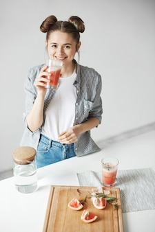 Belle femme avec des petits pains souriant smoothie détox pamplemousse potable sur mur blanc. alimentation saine