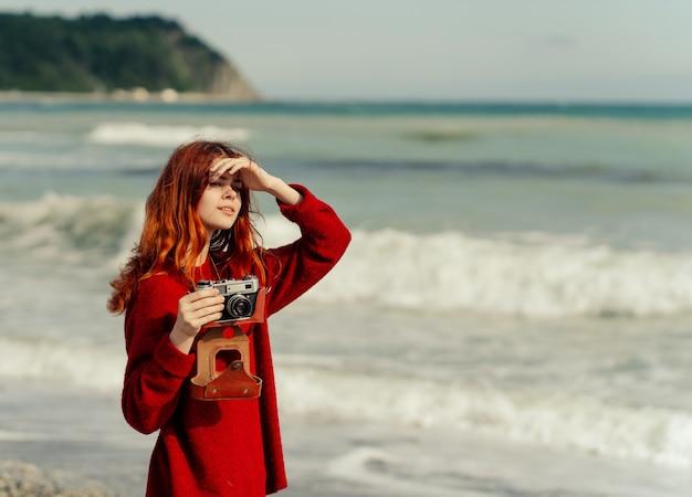 Belle femme photographe aux cheveux roux prend des photos avec un vieil appareil photo